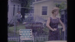 1966: a lady is checking the uniform of a police person standing near to mother Stock Footage