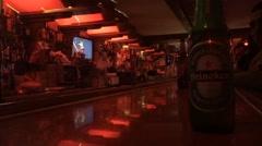 Heineken Beer in Foreground of Dark Bar Stock Footage