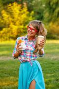 Girl holds cup of coffee and hot dog. Stock Photos