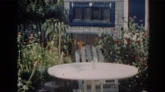 1963: white table and chair in backyard garden during a sunny day NEW JERSEY Stock Footage
