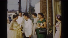 1963: bride and other wedding-goers interact with one another outdoors  Stock Footage