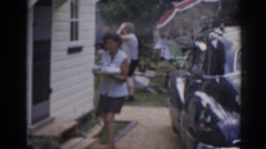 1963: woman bringing leftovers in after outdoor barbecue in the back yard.  Stock Footage