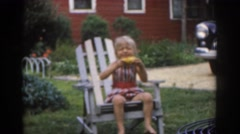 1963: a small child enjoying corn on the cob in the backyard NEW JERSEY Stock Footage