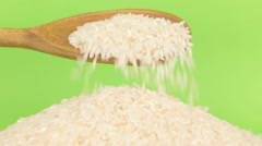 Wooden spoon pours grains rice at heap of rice on a green screen Stock Footage