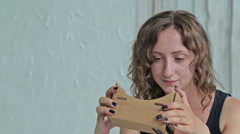 Young woman using Virtual Reality Glasses and sitting on the bed. Dolly shot Stock Footage