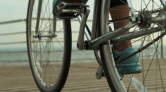 Young woman wearing clothes for sport, riding a bicycle near the sea Stock Footage