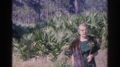 1966: an old woman standing in tall grass in front of a forest on a windy day Stock Footage