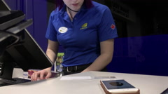 Worker typing customer information for ordering camera inside Best buy store Stock Footage