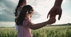 Little Asian girl walking on the green field with their parents, holding hands Stock Footage