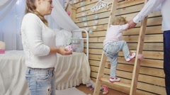 Father helps his baby girl to clamber up at the ladder Stock Footage