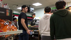 Pan shot of people line up for paying food at 7 eleven check out counter Stock Footage