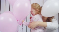 Baby girl and her moter playing with pink and white toy ballons in slow motion Stock Footage
