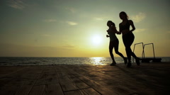 Two slim active ladies running in the evening time Stock Footage