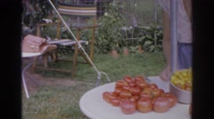 1966: woman in glasses wipes down a table outdoors. NORFOLK VIRGINIA Stock Footage