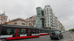 Two modern red trams passing Dancing House in Prague Stock Footage