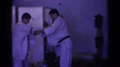 1966: two men attempting to demonstrate a martial arts throw and failing. TEMPLE Stock Footage