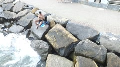 Young shirtless athletic man sitting on rock by sea Stock Footage