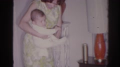 1966: a mother holding her newborn baby in the living room TEMPLE CITY Stock Footage