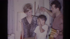 1966: several people gathered in the living room with a man holding bongos Stock Footage