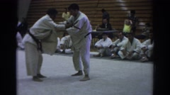 1966: two men competing in martial arts competition while peers watch TEMPLE Stock Footage
