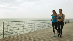 Young ladies wearing trendy clothes for sport, running near the sea Stock Footage