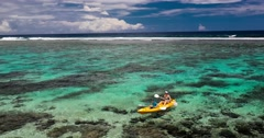 Female and little boy paddling canoe on a lagoon with coral reef Stock Footage