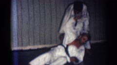 1966: a man throws another man down on the mat at a karate competition with flag Stock Footage