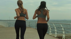 Best friends running together, wearing similar sport clothes and listening to Stock Footage
