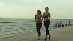 Young brunette girl running with her best friend with beautiful blond hair near Stock Footage