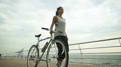 Young active brunette holding bycicle in her hand, while posing on camera Stock Footage