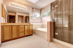 Luxury bathroom interior in soft peach colors with modern appliances and carp Stock Photos