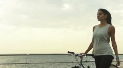 Active woman holding bycicle in her handand having fun near the sea Stock Footage