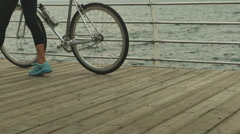 Young girl wearing trendy sport clothes , holding bycicle in her hand Stock Footage