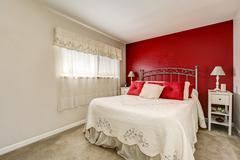 Bright woman's bedroom with red contrast wall, iron bed with elegant bedding  Stock Photos