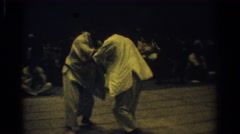 1966: two rivals in a crowded martial arts class wrest each other to the ground Stock Footage