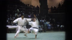 1966: two men engaging in a martial arts demonstration before an audience WEST Stock Footage