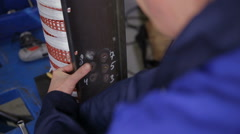 Factory worker assembling electric equipment - transformer - on assembly Line Stock Footage