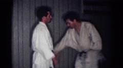 1967: men practicing karate wearing robes fighting LOS ANGELES CALIFORNIA Stock Footage