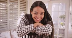 Pretty latina woman sitting at home smiling at camera Stock Photos