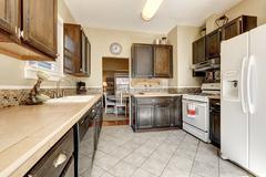 Kitchen room - dark brown cabinets, tile floor and white appliances. Northwes Stock Photos