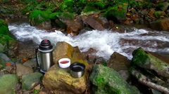 Thermos of tea near a mountain stream Stock Footage