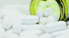 Pill bottle on its side with white tablet pills overflowing Stock Footage