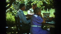 1939: family meal with 6 people on a sunny day outside on a picnic table AUBURN Stock Footage