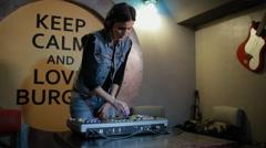 Woman DJ tweak different track controls on dj's deck at bar Stock Footage
