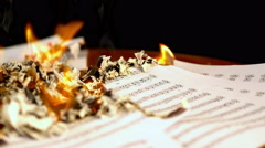 Sheet music are burning on background of girl playing violin. 4k. Stock Footage