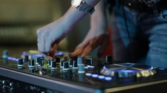 Female hands of DJ tweak track controls on dj's deck, camera is breathing Stock Footage
