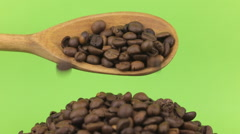 Wooden spoon pours coffee beans at heap of coffee beans on a green screen Stock Footage