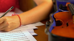 Girl composes music in music sheet book . Stock Footage
