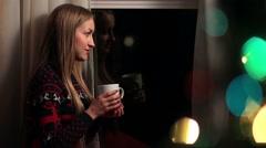 Beautiful woman drinking coffee on Xmas Eve Stock Footage