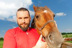 Close-up portrait of happy man with his bay horse Stock Photos